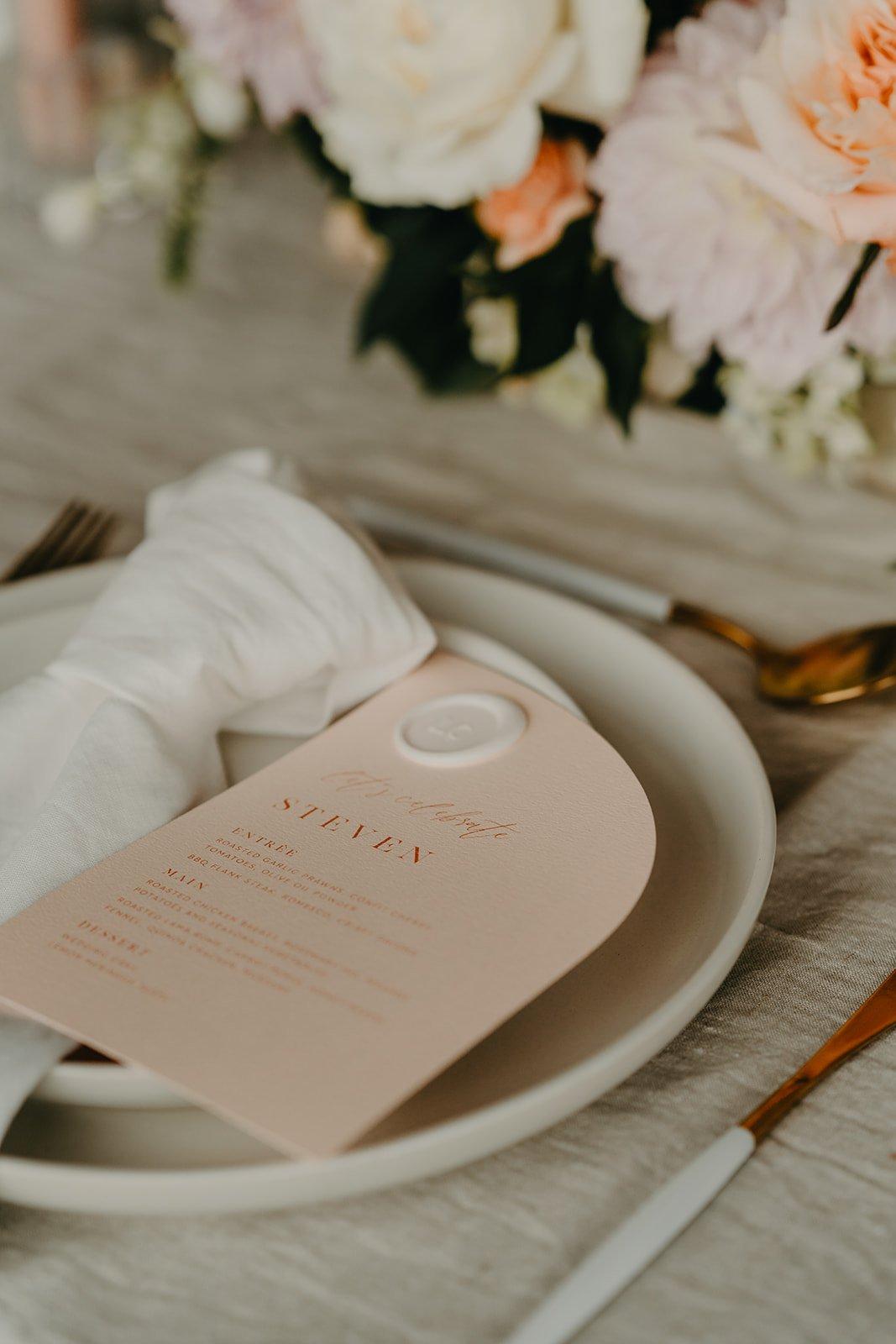 peach invitation with wax seal half arch